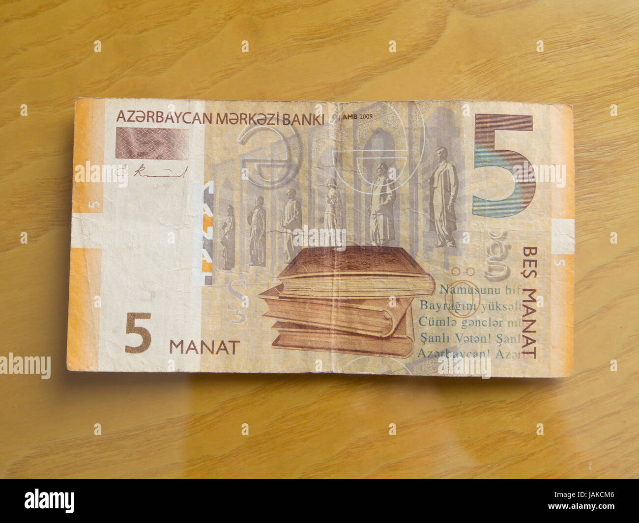 Azerbaijani currency, five manat, isolated on a wooden table - Stock Image