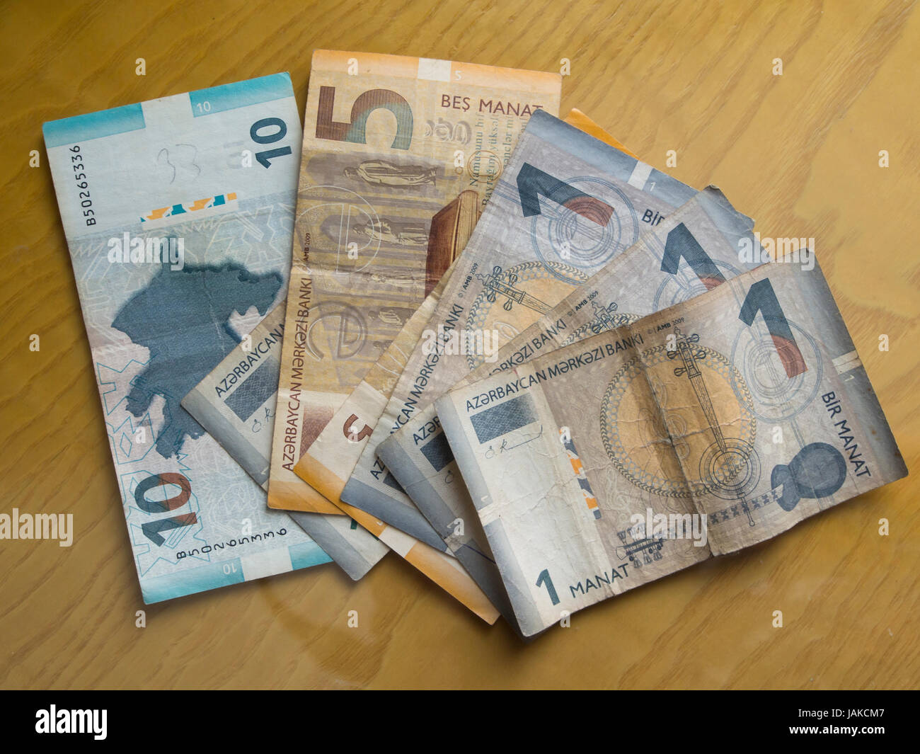 Azerbaijani currency, manat, isolated on a wooden table, fan of 1, 5 and 10 banknotes - Stock Image