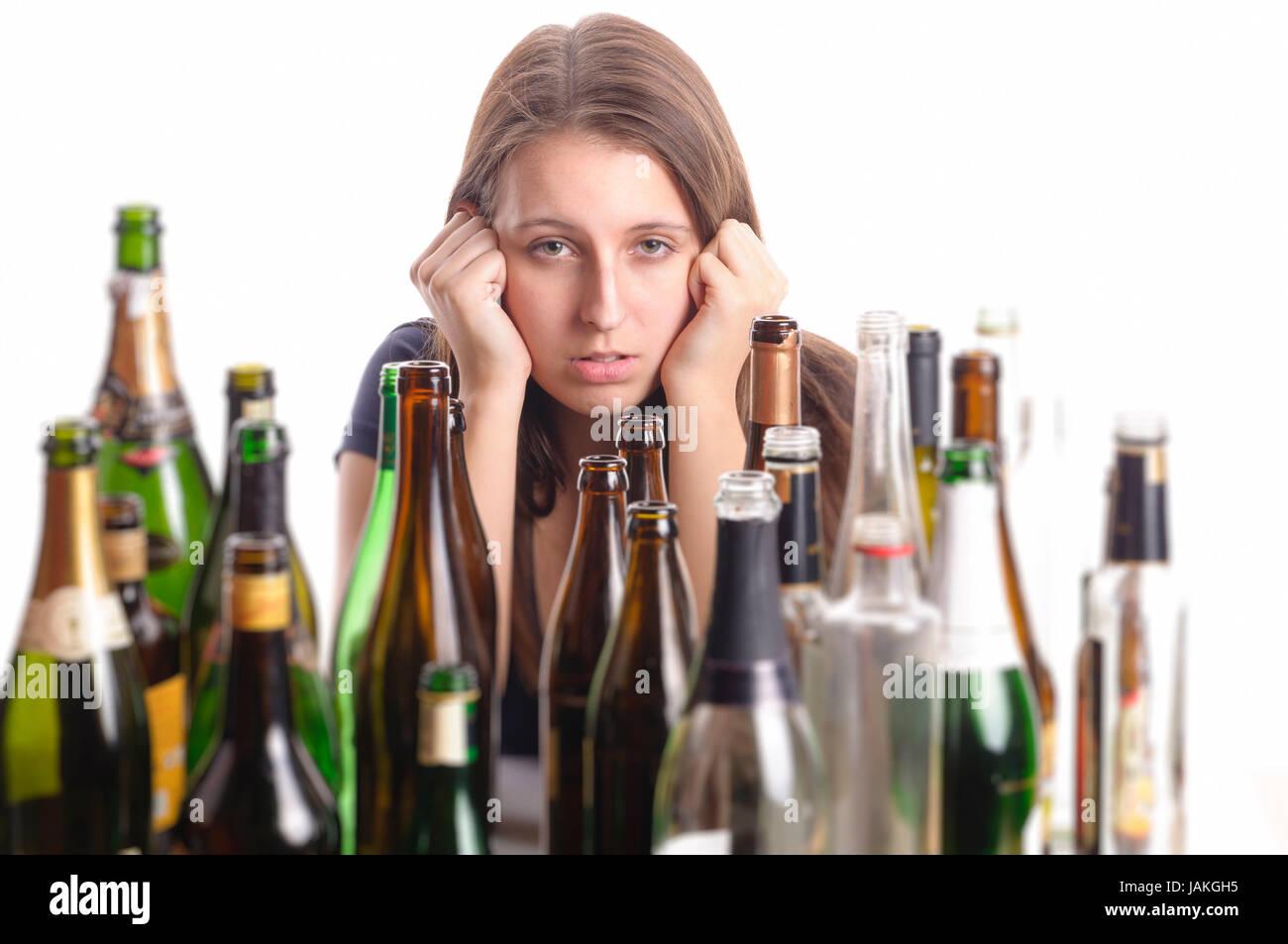 Eine junge Frau mit brünetten langen Haaren sitzt inmitten von leeren Flaschen an einem Tisch und sieht verzweifelt - Stock Image