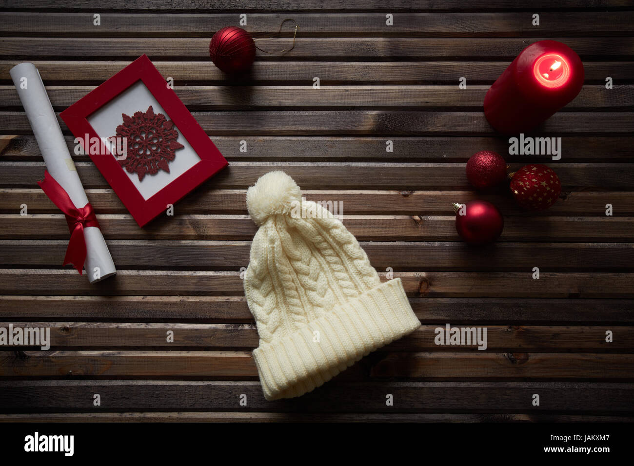 Image of red snowflake in frame, decorative toy balls, white cap, burning candle and rolled paper wrapped with red - Stock Image