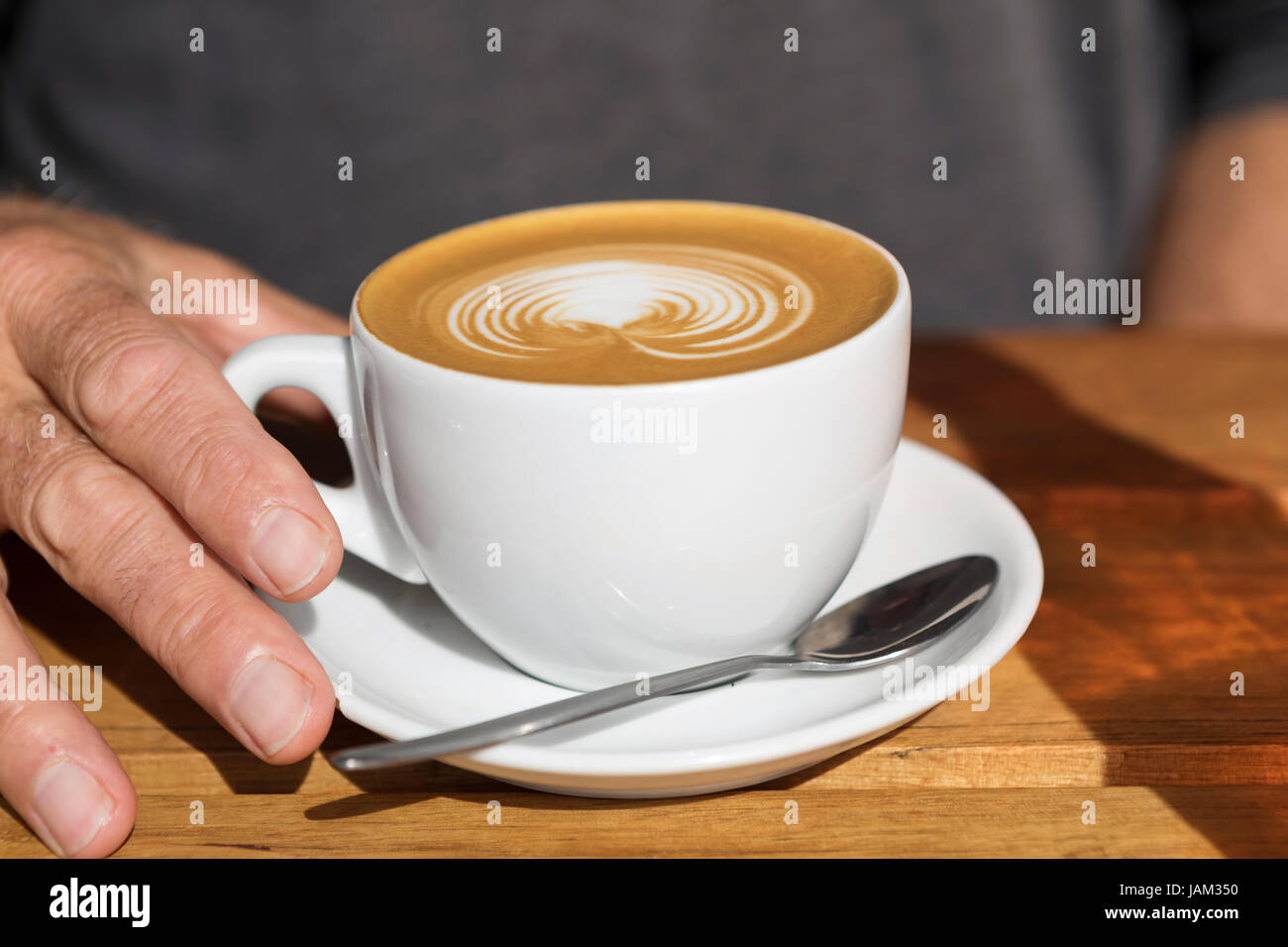 man's hand on the handle of a cup of latte with a design and a spoon on the plate - Stock Image