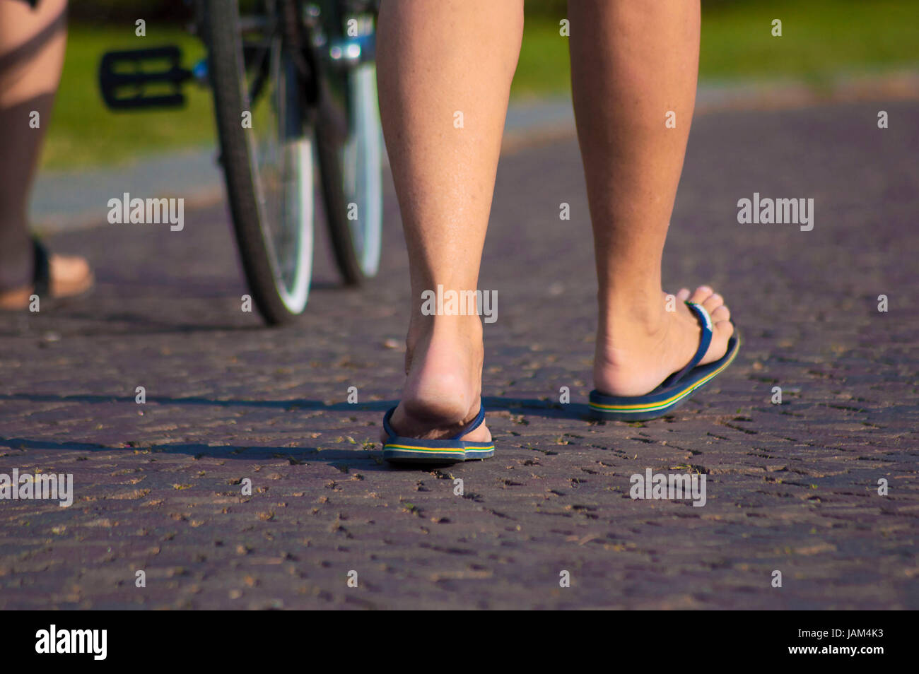 f3500af7149b4b Girl with flip flops walking on the street of como city - Stock Image
