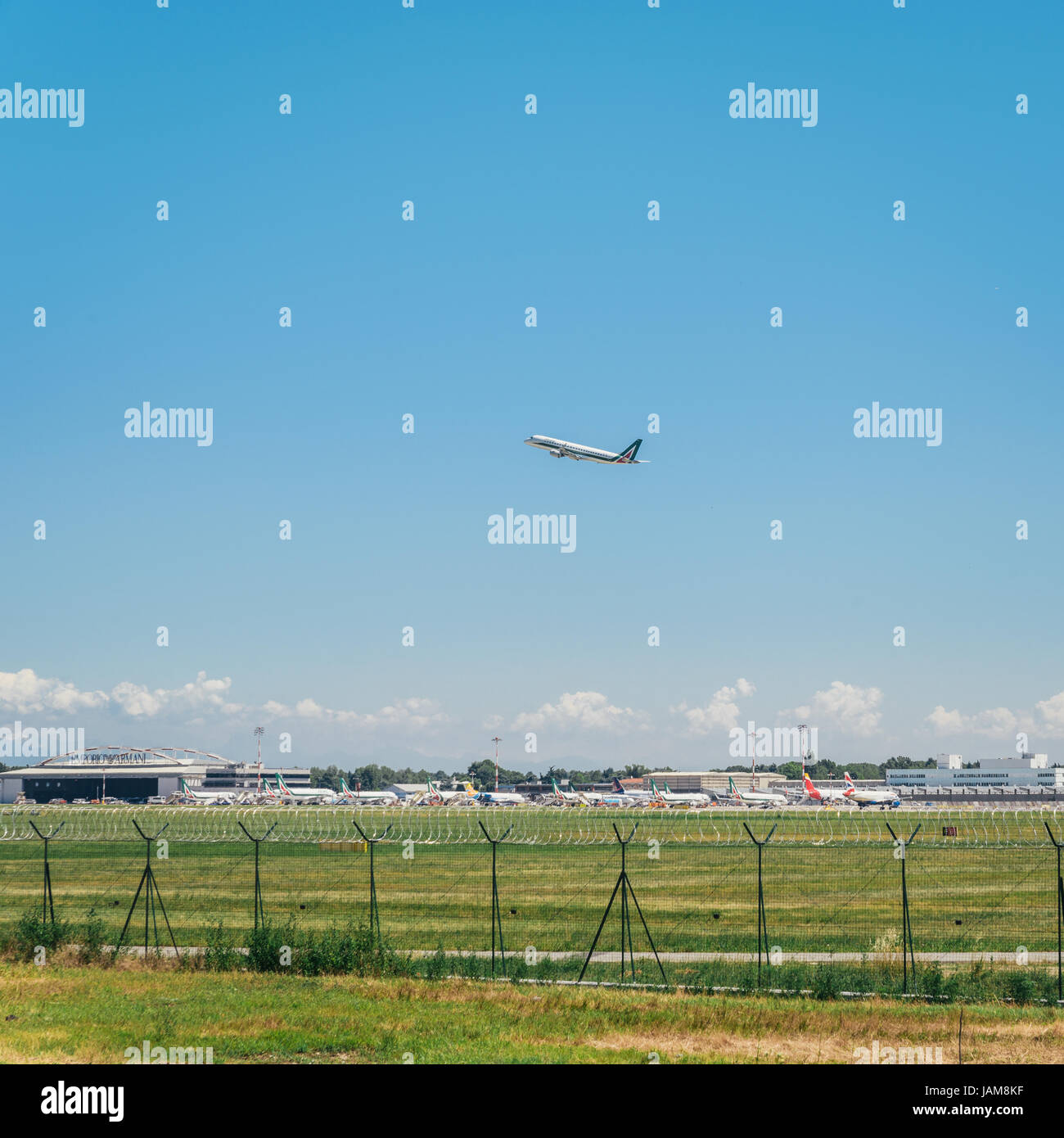 Alitalia commercial airplane takes off from Milan's Linate Airport in Italy during a beautiful summer day, where - Stock Image
