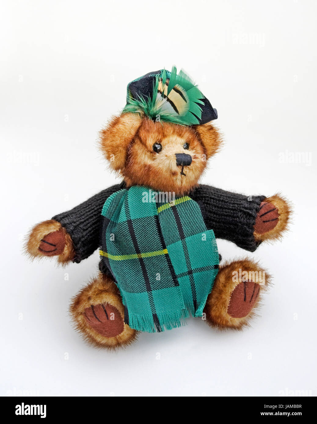Cute cuddly Scottish teddy bear wearing woolly jumper, tartan scarf, and beret with tartan feather plume. - Stock Image