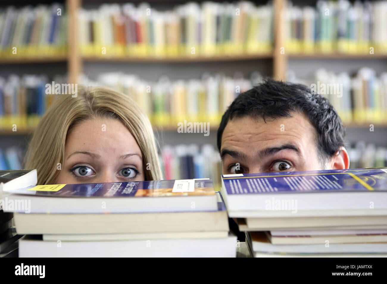 University,library,student,couple,book batch,hervorspähen,portrait,detail,ocular match,uncertainly,anxiously,lend,stacked - Stock Image
