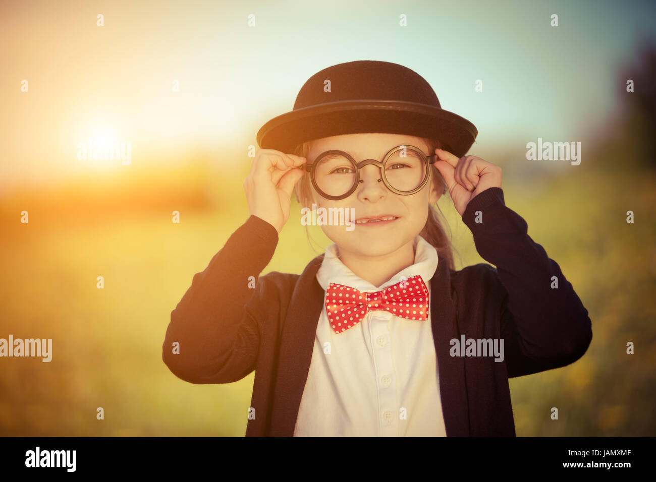 Funny little girl in glasses, bow tie and bowler hat. - Stock Image
