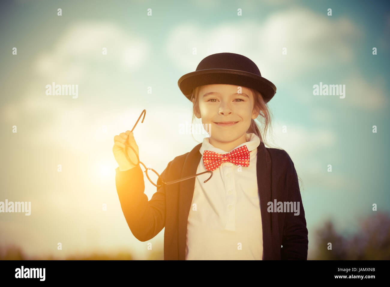 Funny little girl in bow tie and bowler hat. - Stock Image