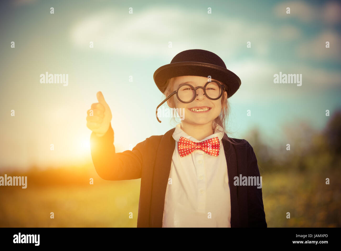Funny little girl in bow tie and bowler hat showing thumb up. - Stock Image