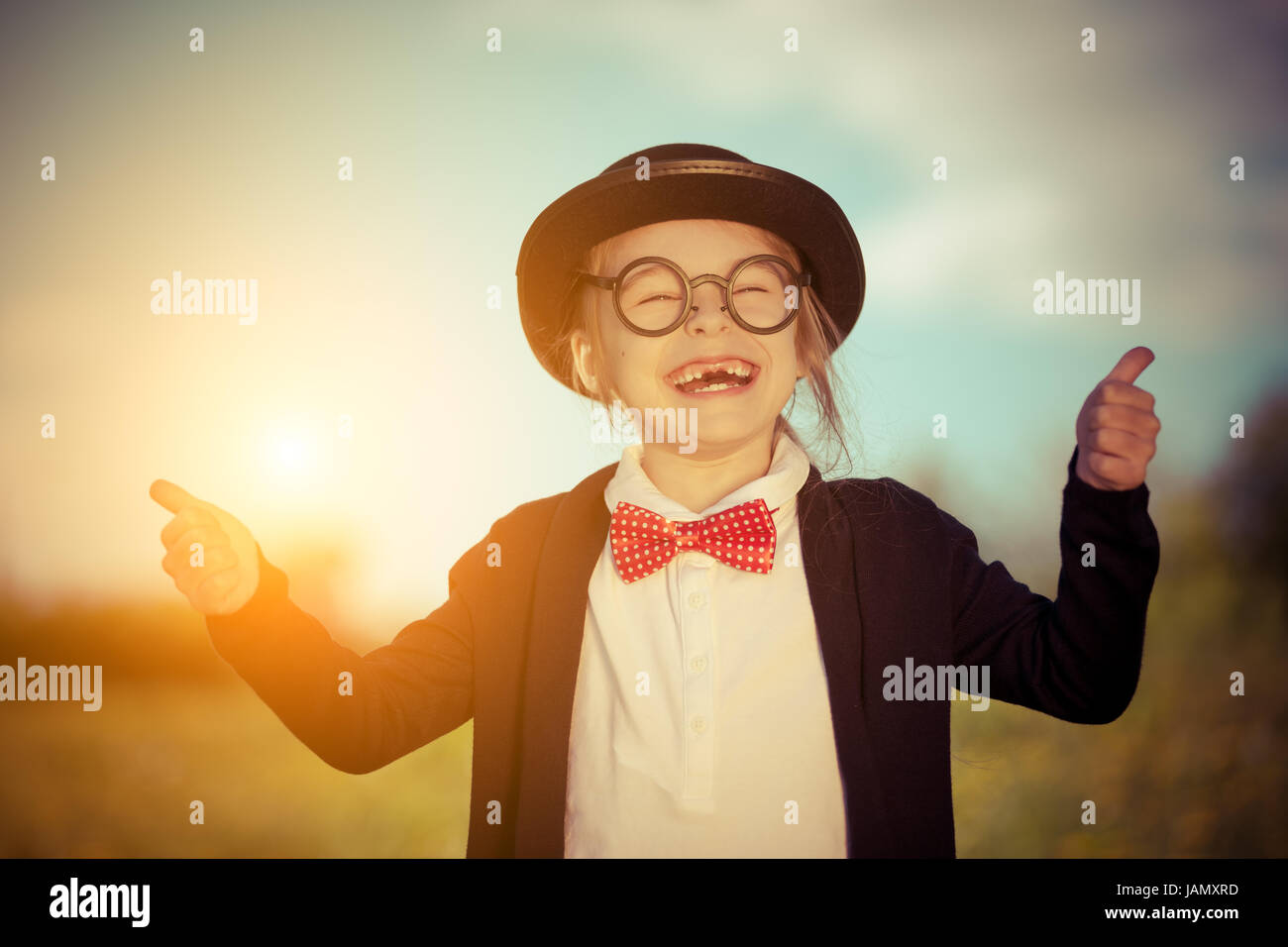 Funny little girl in bow tie and bowler hat showing thumbs up. - Stock Image