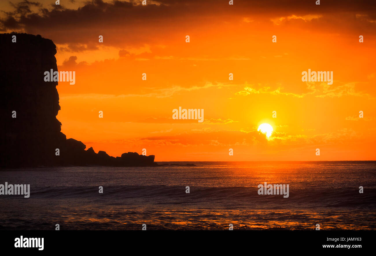 Bright orange red sun rising through clouds over Pacific ocean horizon off Avalon beach in Sydney Northern beaches. - Stock Image