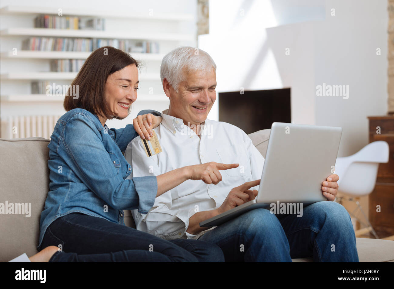 Mature Couple connected with laptop and shopping online - Stock Image