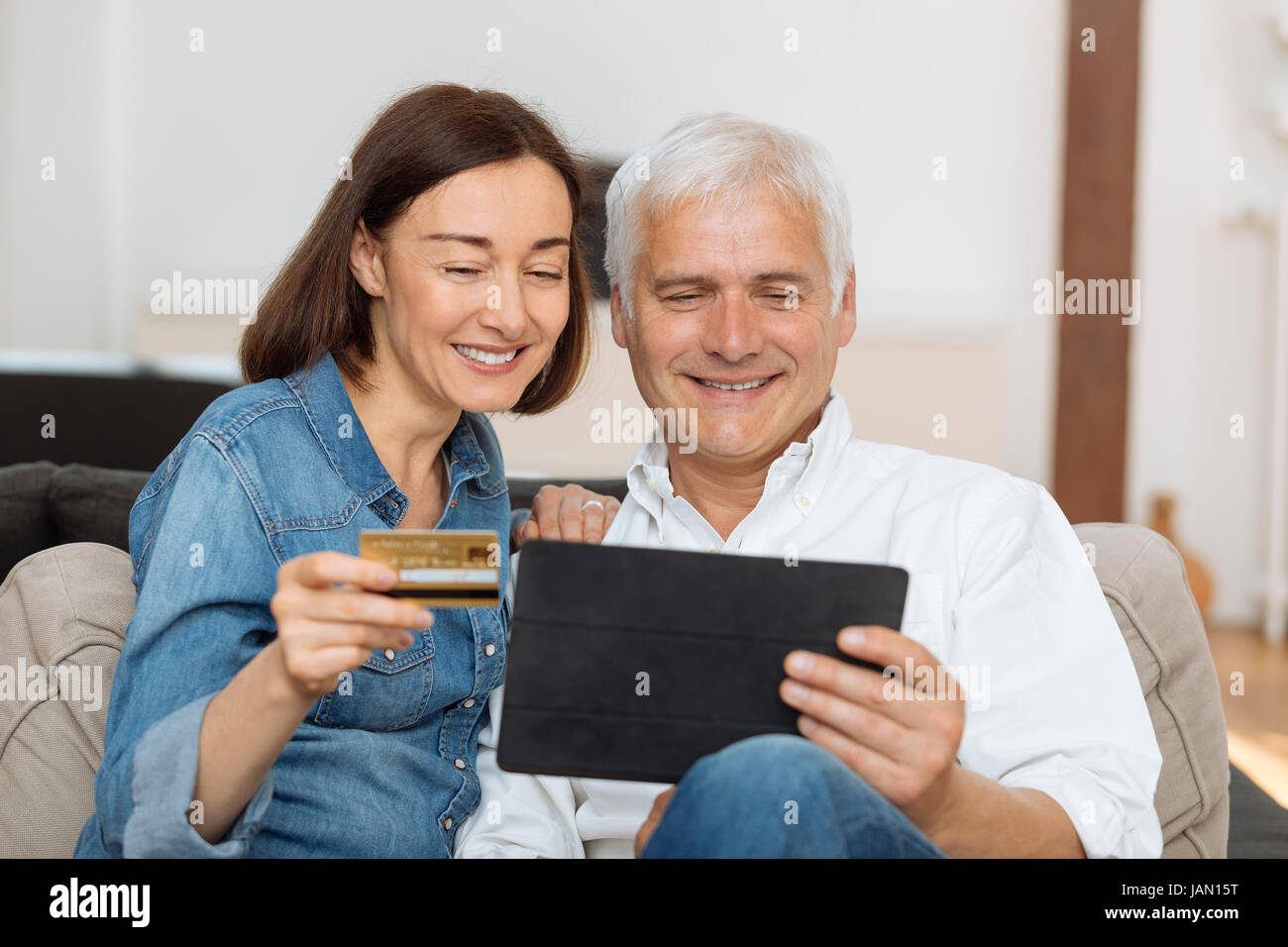 Mature couple using credit card to shop online - Stock Image