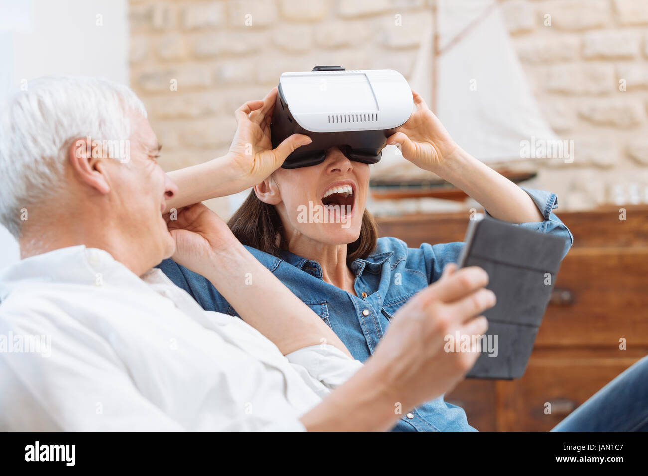 Mature couple using digital tablet and virtual reality headset in living room - Stock Image