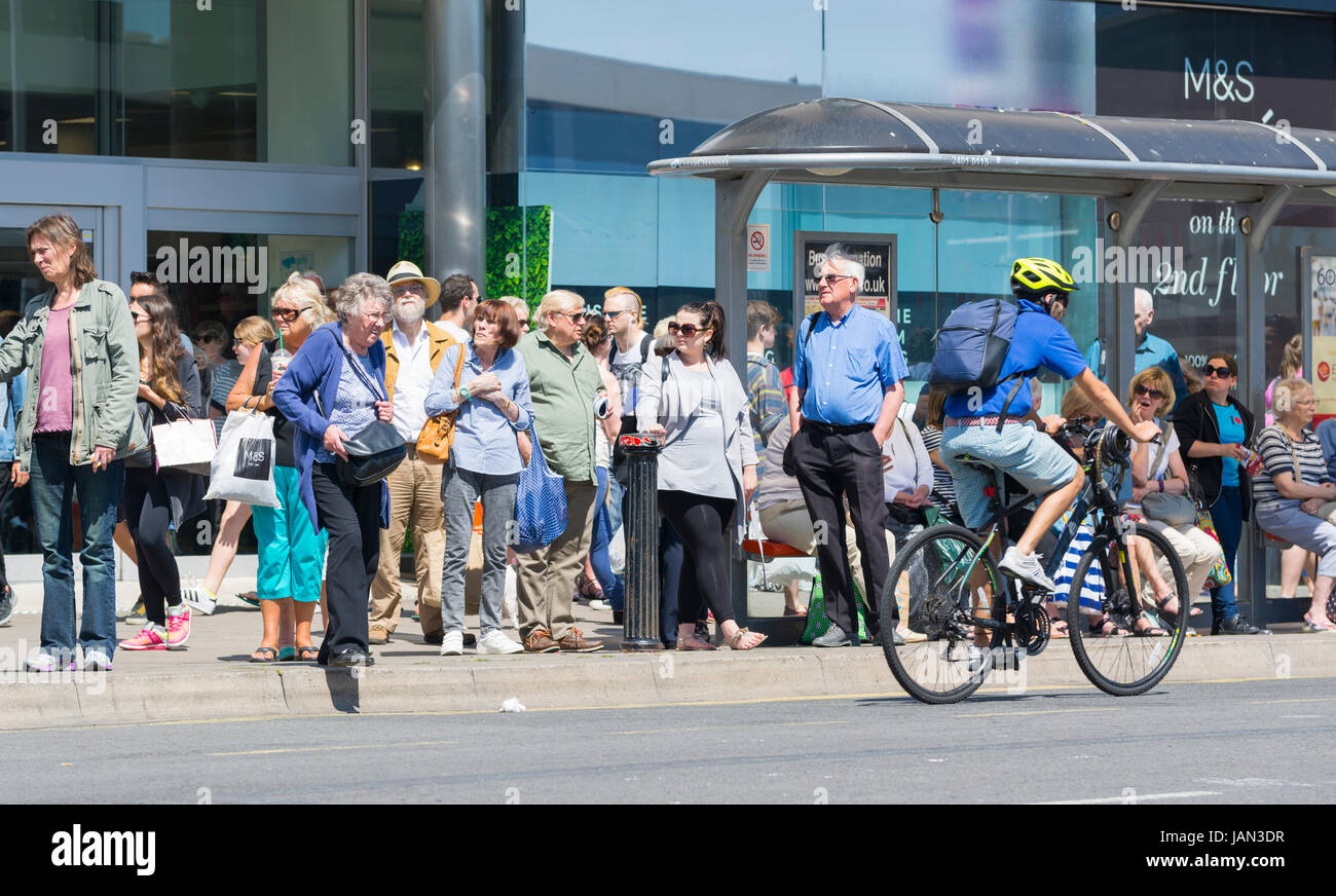 Line of people queueing at a bus stop in the UK. Stock Photo