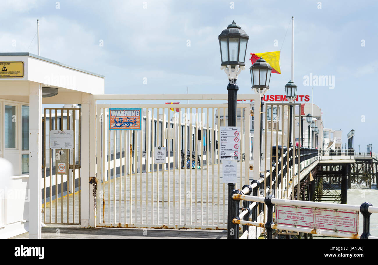 Worthing Pier with gates shut as it is closed during the day due to strong winds. - Stock Image