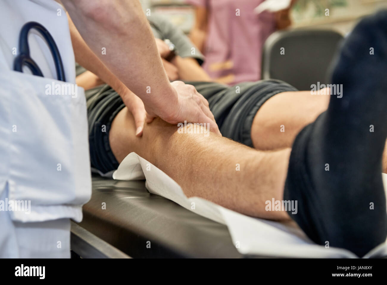 orthopedist is checking a knee by scanning with the hands - Stock Image