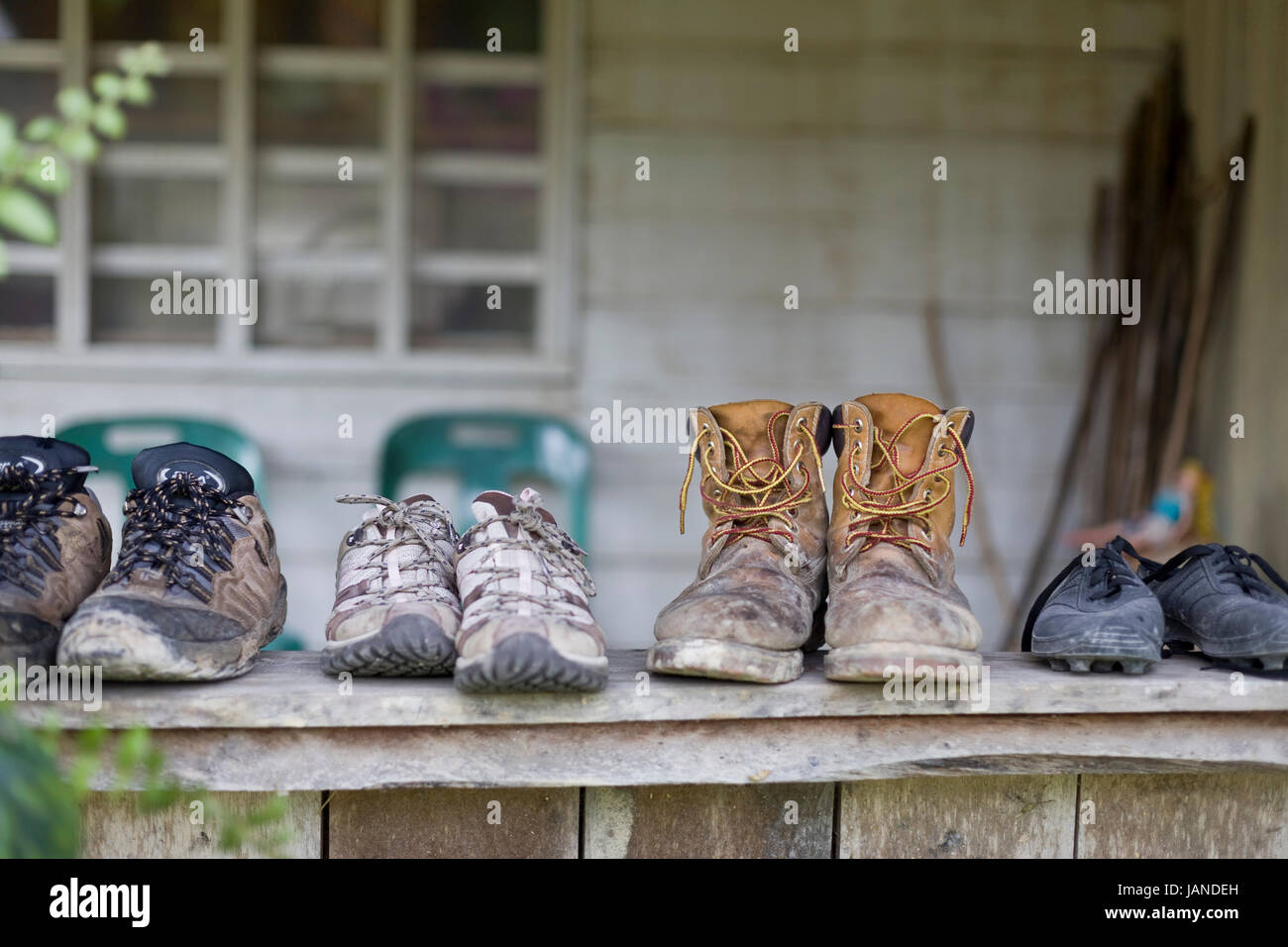 Muddy boots on a patio - Stock Image