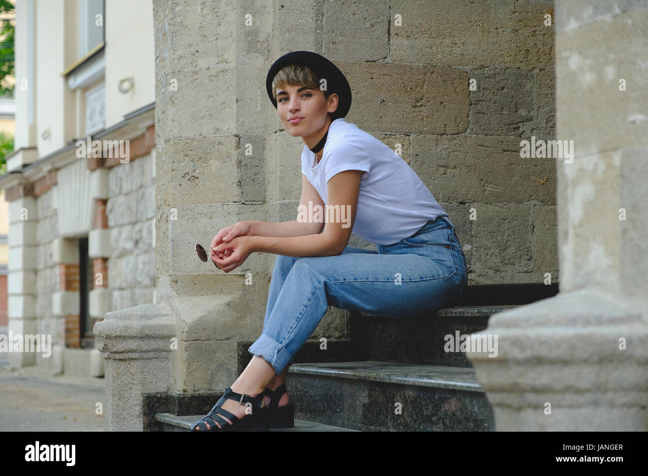 Close up portrait of female hipster with natural makeup and short haircut enjoying leisure time outdoors Stock Photo