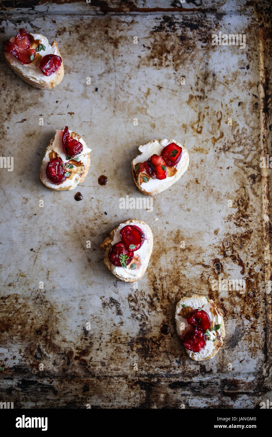 Roasted cherries and labneh crostini - Stock Image