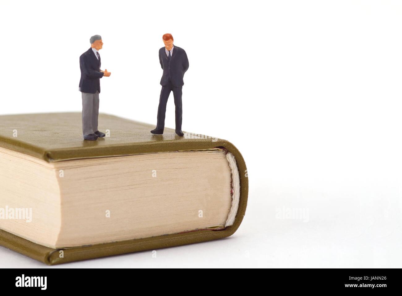 Stehende Miniaturfiguren auf  Buch freigestellt auf weissem Hintergrund Stock Photo