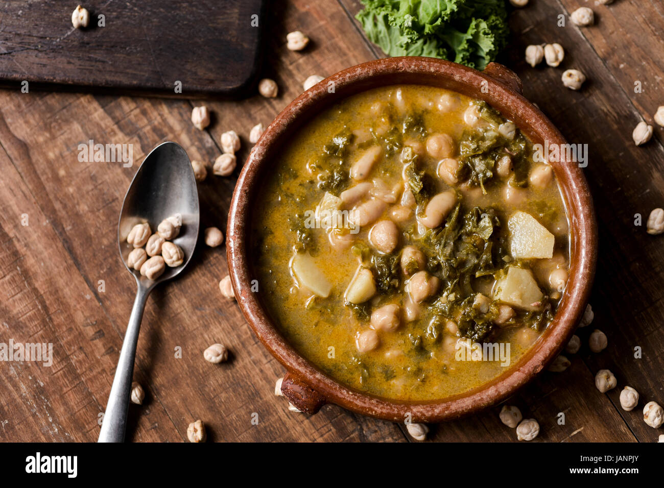 closeup of an earthenware bowl with kale stew with potatoes and chickpeas, on a rustic wooden table sprinkled with - Stock Image