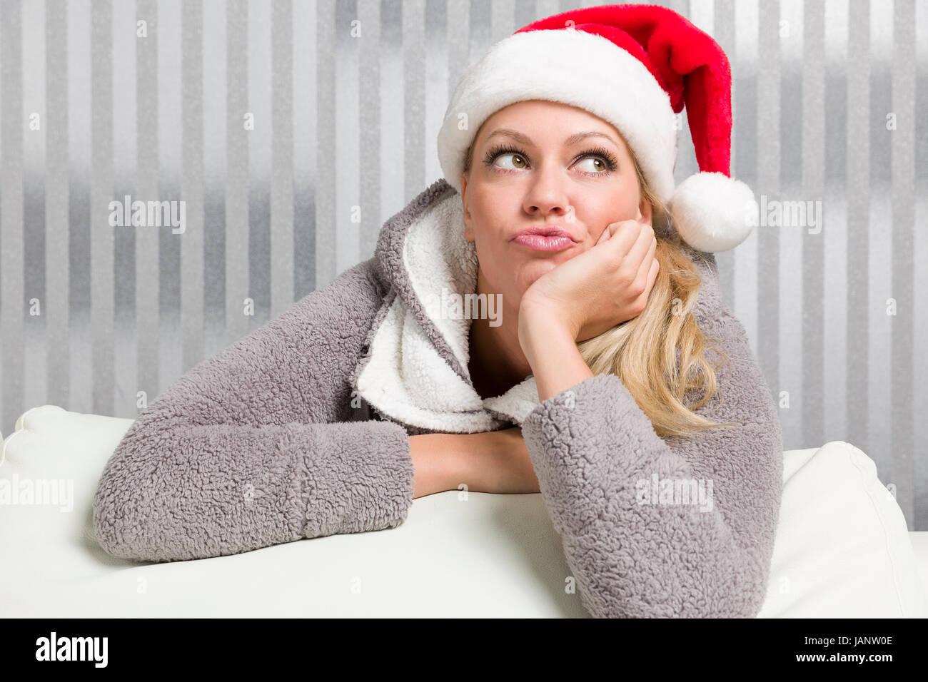 Frau mit Weihnachtsmütze überlegt was sie zu Weihnachten verschenken kann, ist allerdings einfallslos. - Stock Image