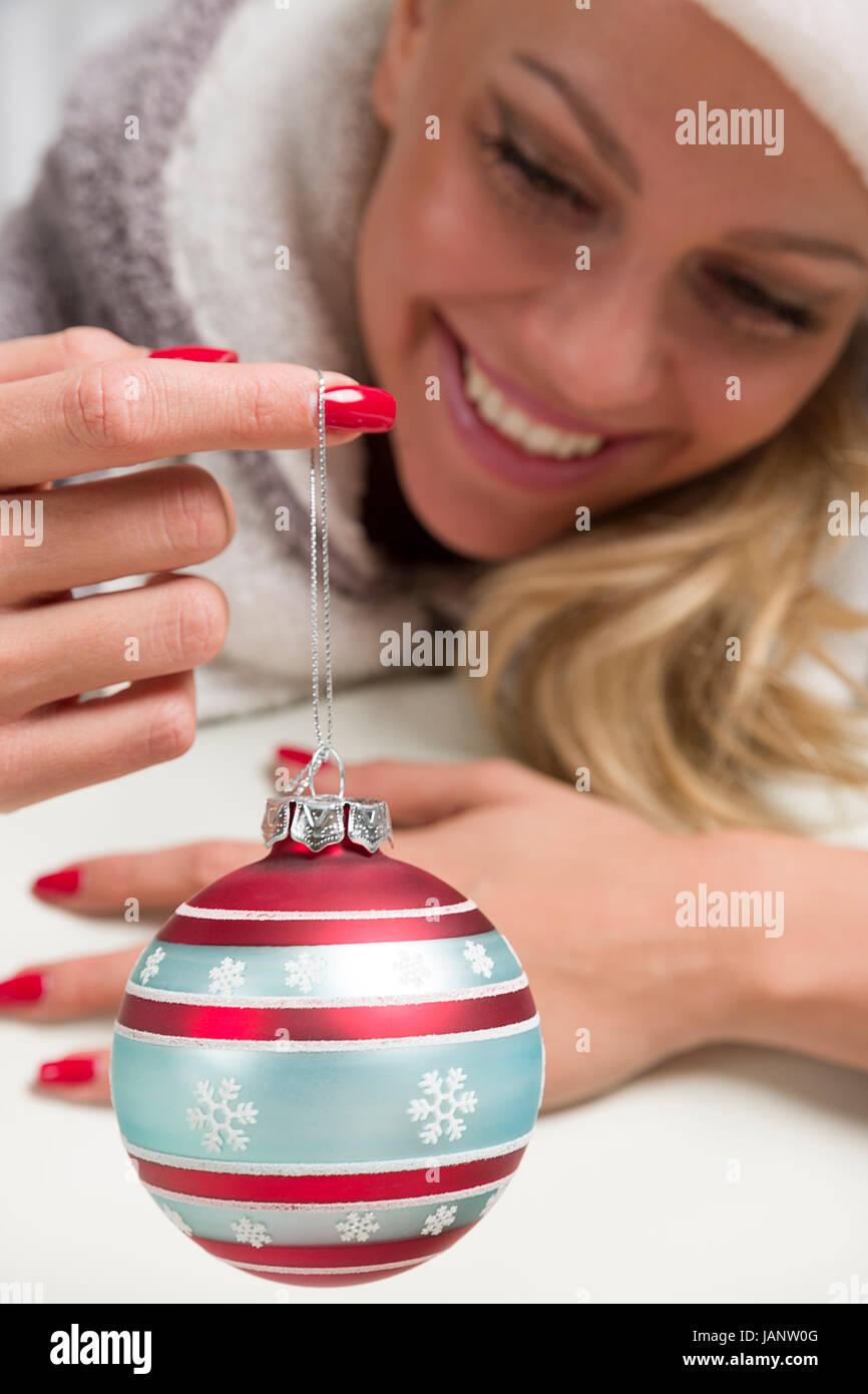 Frau mit Weihnachtsmütze hält schaut sich eine Christbaumkugel an die an ihrem Finger baumelt und denkt - Stock Image