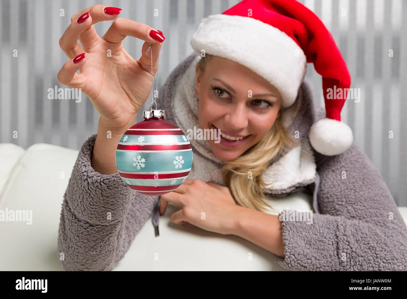 Frau mit Weihnachtsmütze hält eine Christbaumkugel und denkt schon freudig an Weihnachten - Stock Image