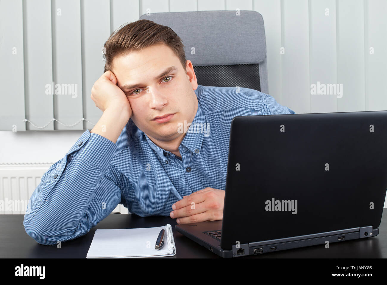 Picture of an exhausted young businessman at the office - Stock Image