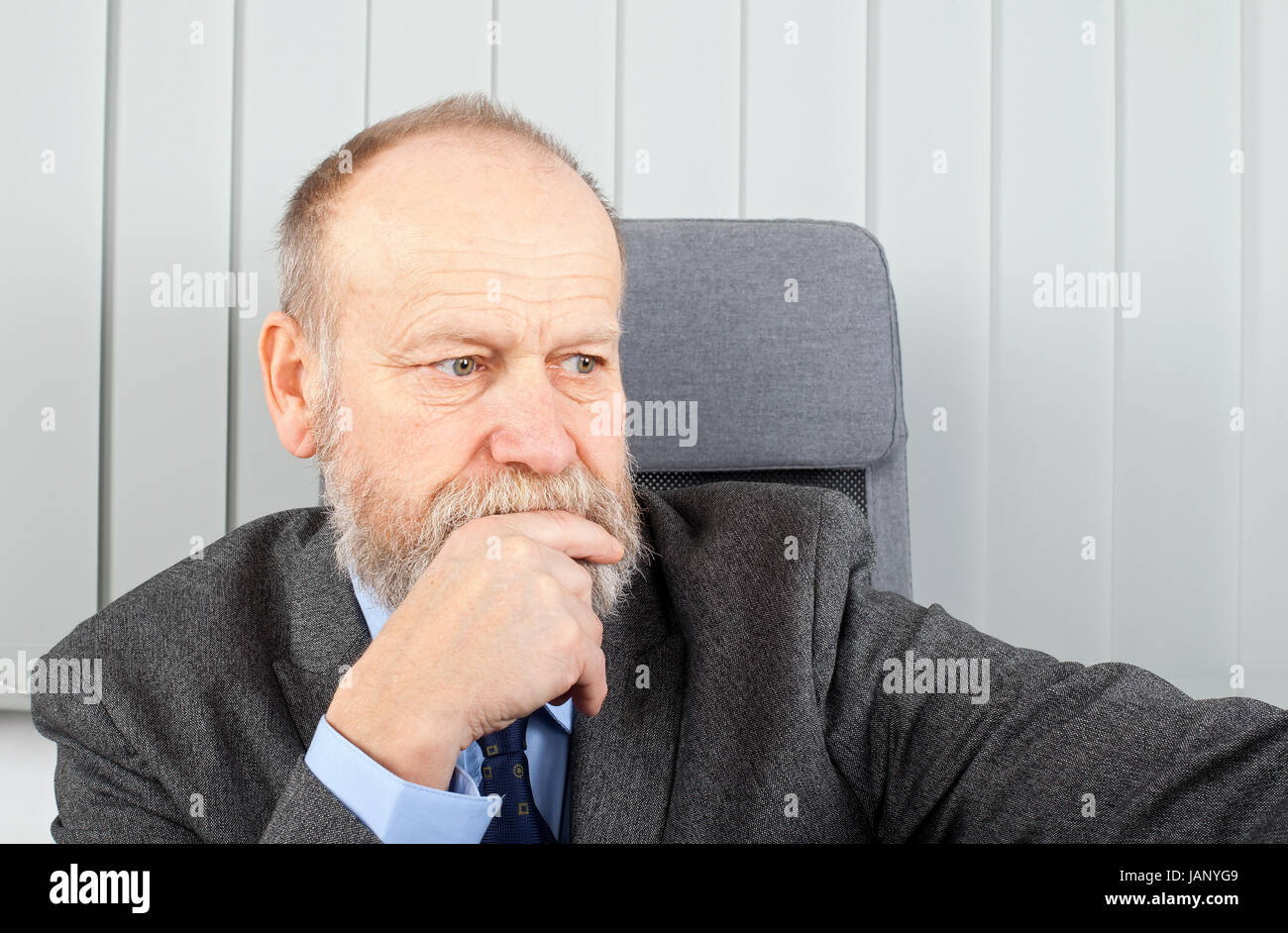 Portrait of a thoughtful businessman at the office - Stock Image