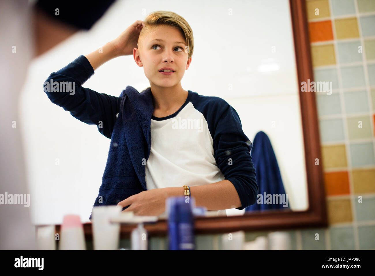 Young caucasian boy set hair with mirror in bathroom - Stock Image