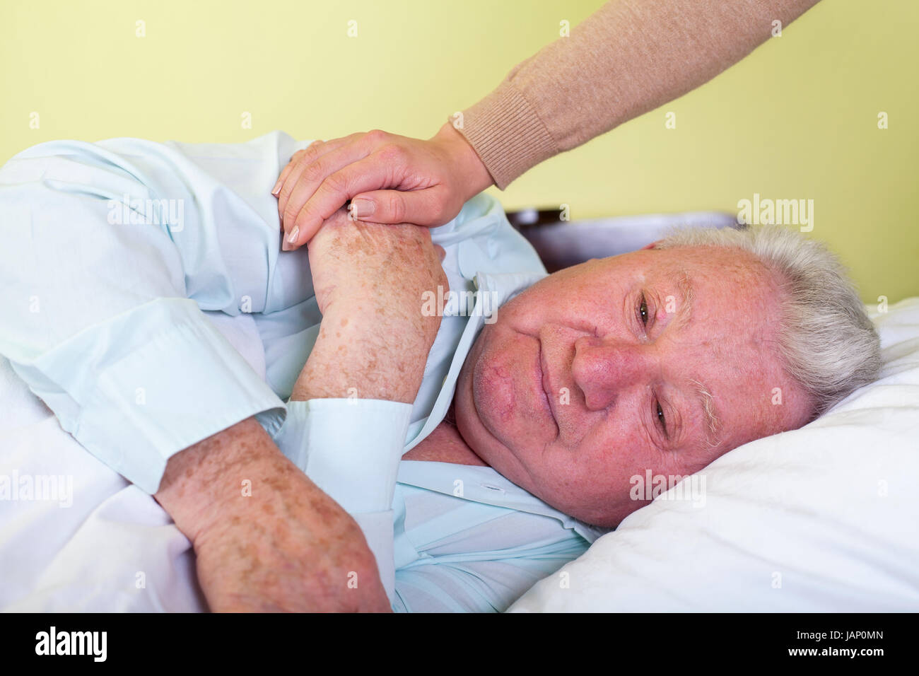 Picture of a depressed old man in bed with his caregiver - Stock Image