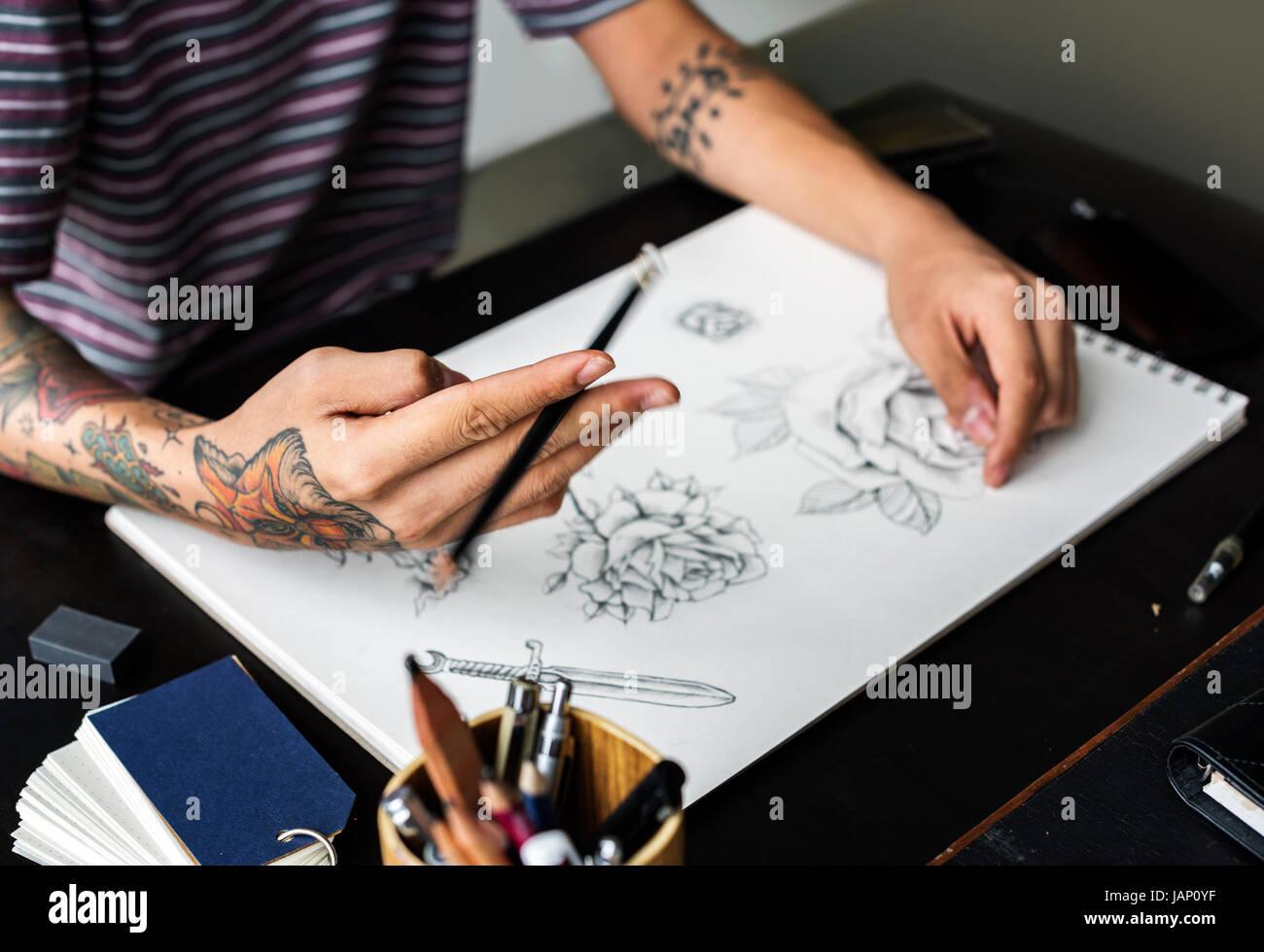 bddee6680 Closeup of tattooed hand with drawing artwork Stock Photo: 144313219 ...