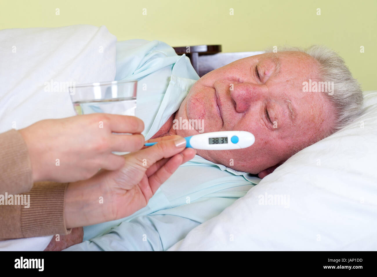 Picture of a sick old man in bed having fever - Stock Image