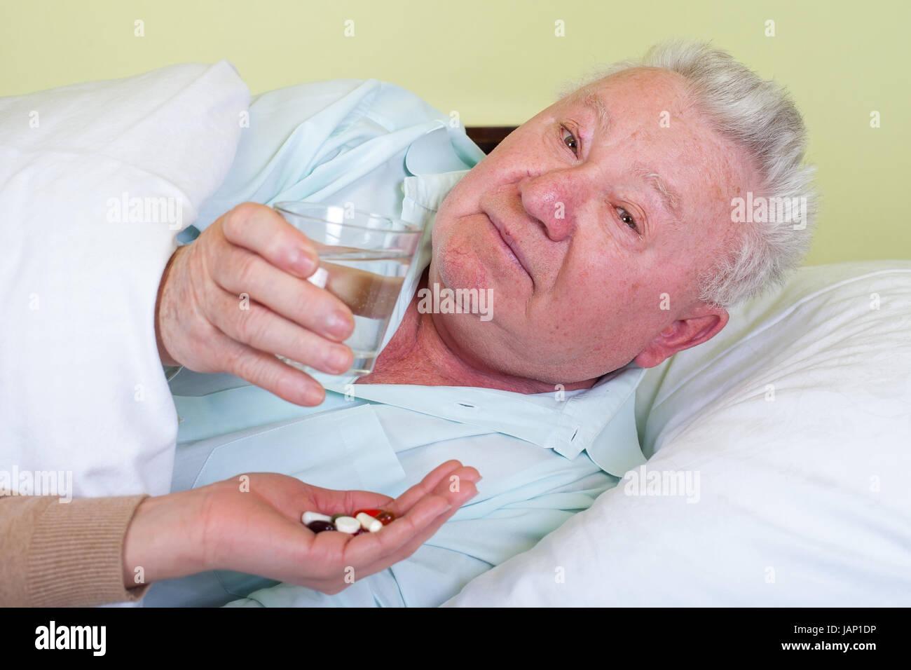 Picture of a bedridden elderly patient receiving his pills - Stock Image