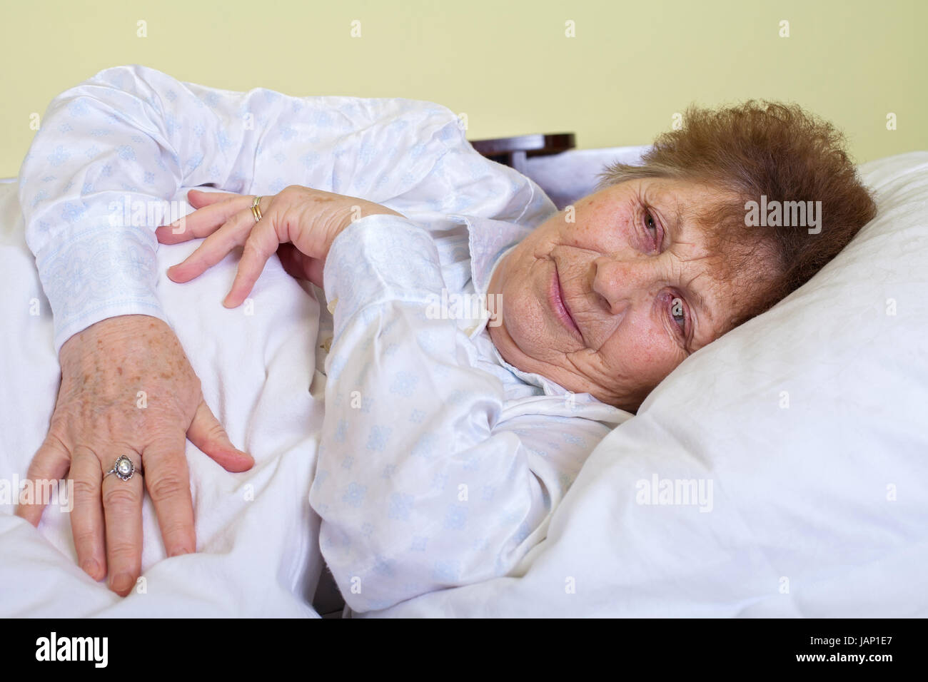 Picture of a sick elderly woman lying in bed - Stock Image