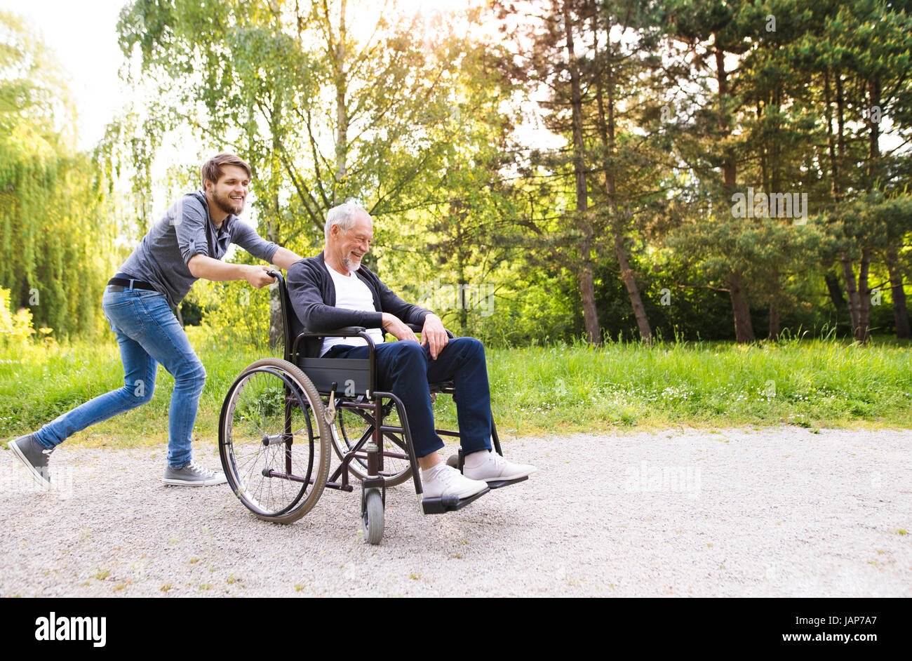 Hipster son running with disabled father in wheelchair at park. - Stock Image