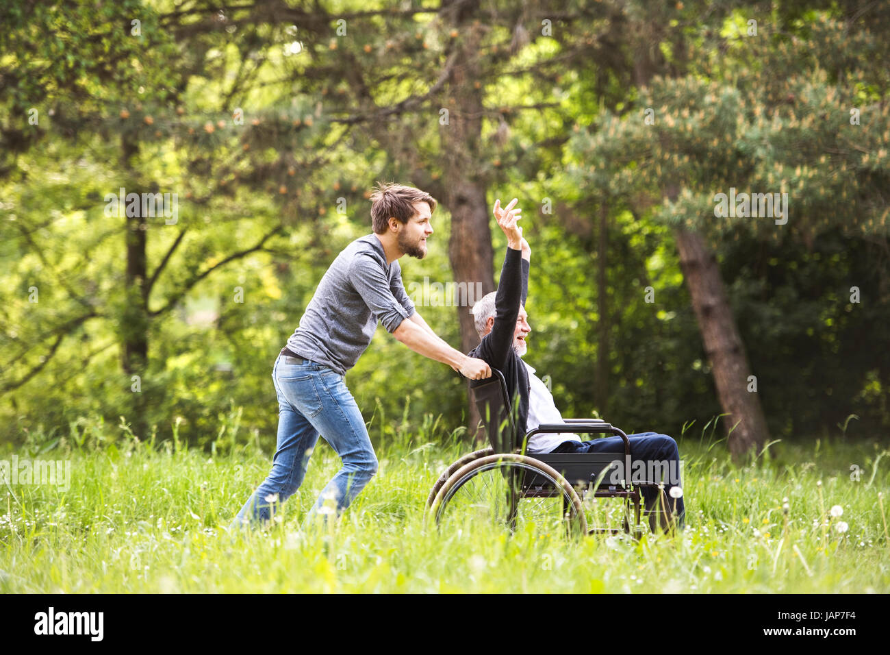 Hipster son walking with disabled father in wheelchair at park. - Stock Image