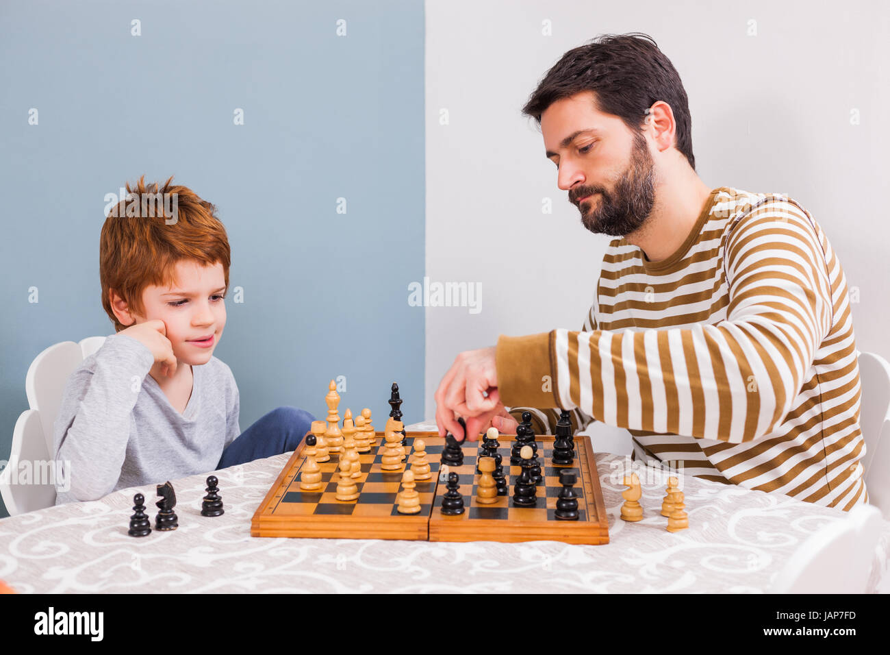 Father and son are playing chess at home. - Stock Image