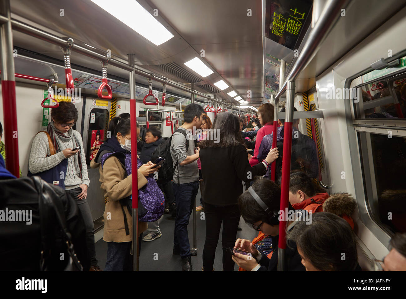 Passengers on their smartphones on MTR underground train system, Hong Kong, China - Stock Image