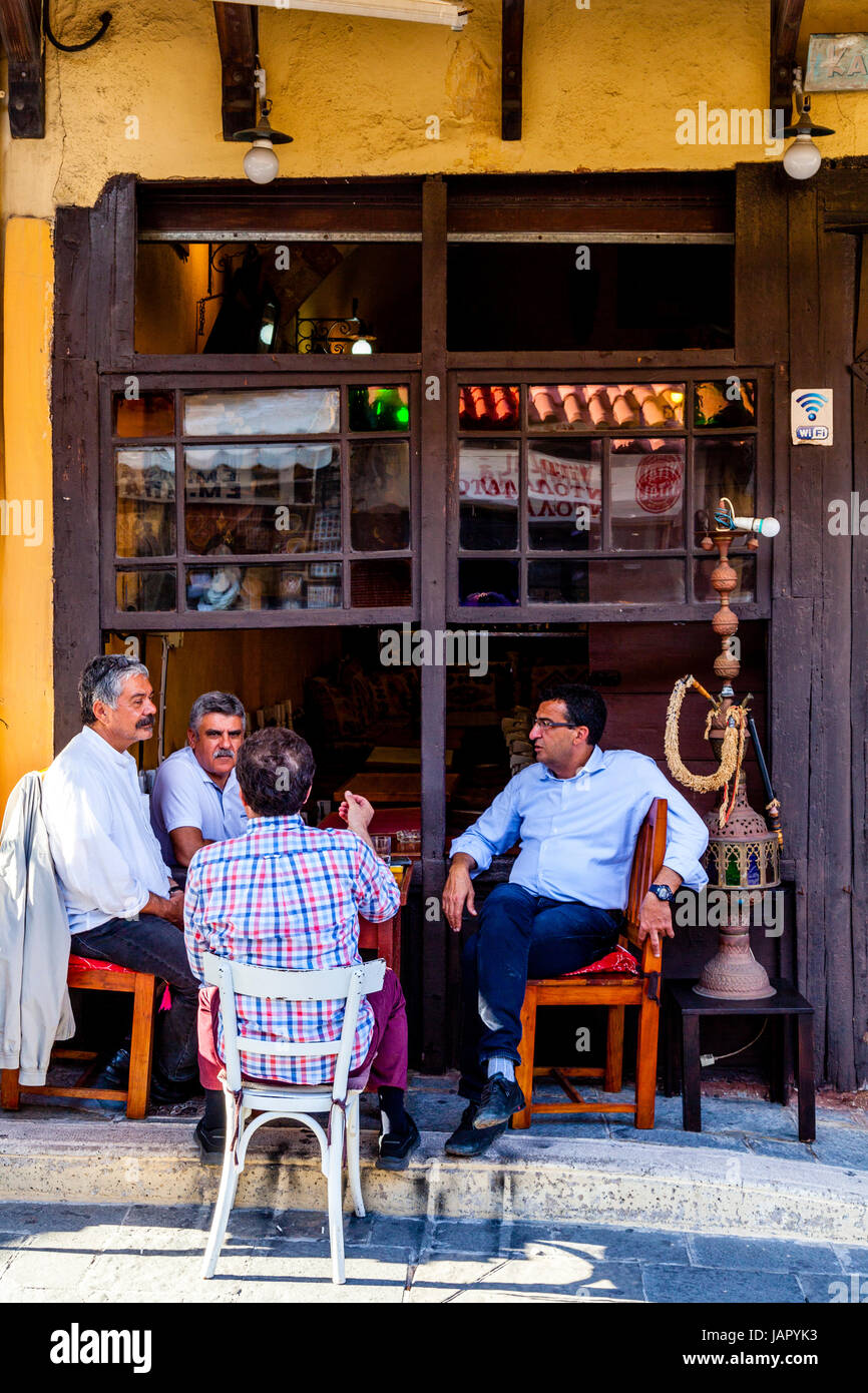 Greek Man Sit Chatting Outside A Cafe On Sokratous Street, Rhodes Old Town, Rhodes, Greece Stock Photo