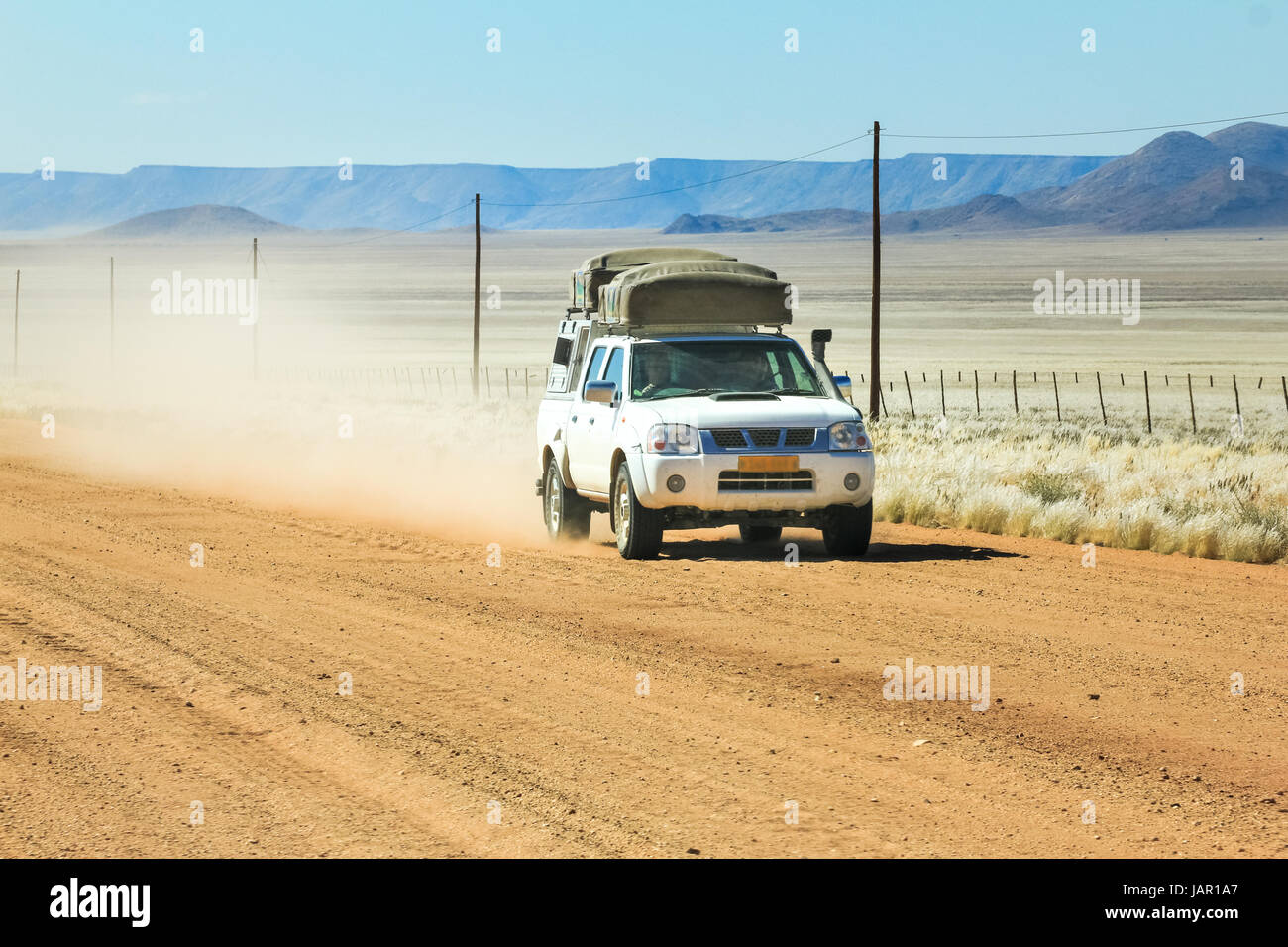 Pickup truck driving fast with dust cloud on desert road - Stock Image