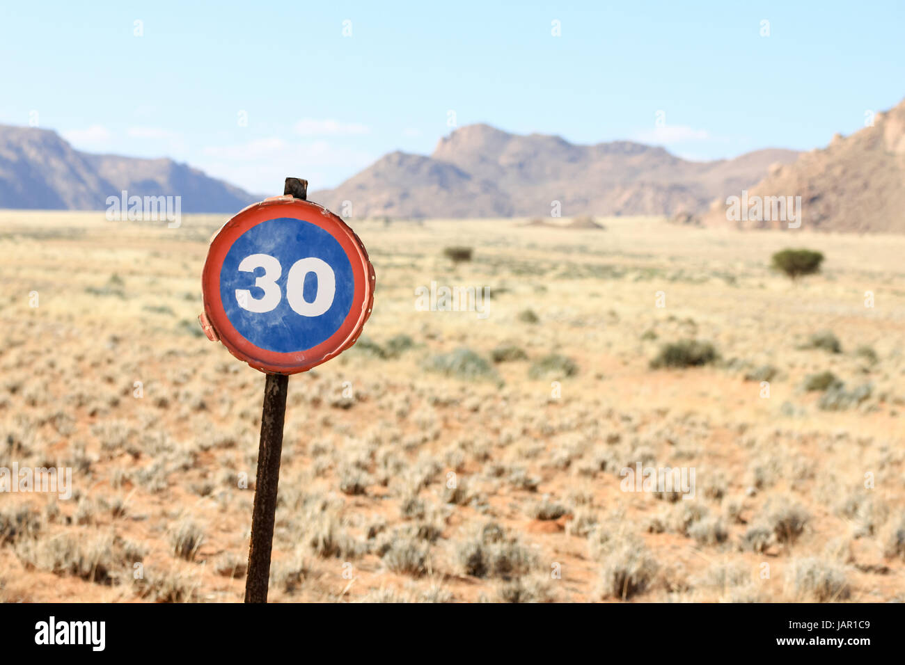 Old speed road sign in desert and mountain landscape Stock Photo