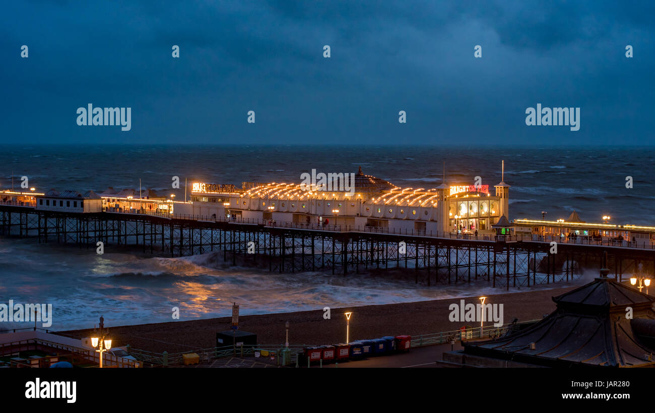 View of Brighton pier floodlit at night - Stock Image