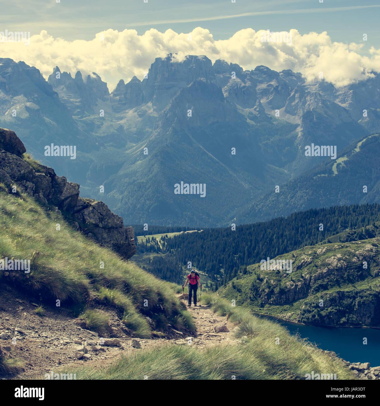 Trekker walking a picturesque mountain trail. - Stock Image