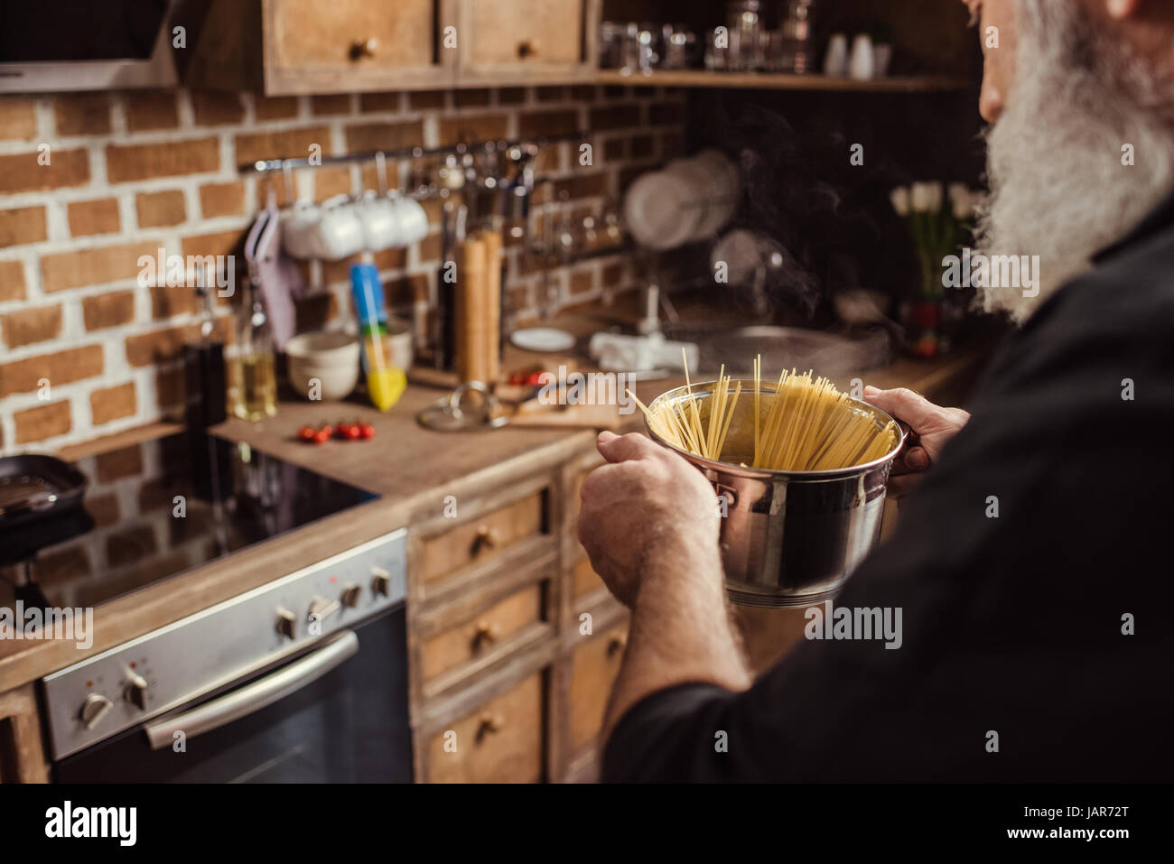 Man cooking spaghetti   - Stock Image