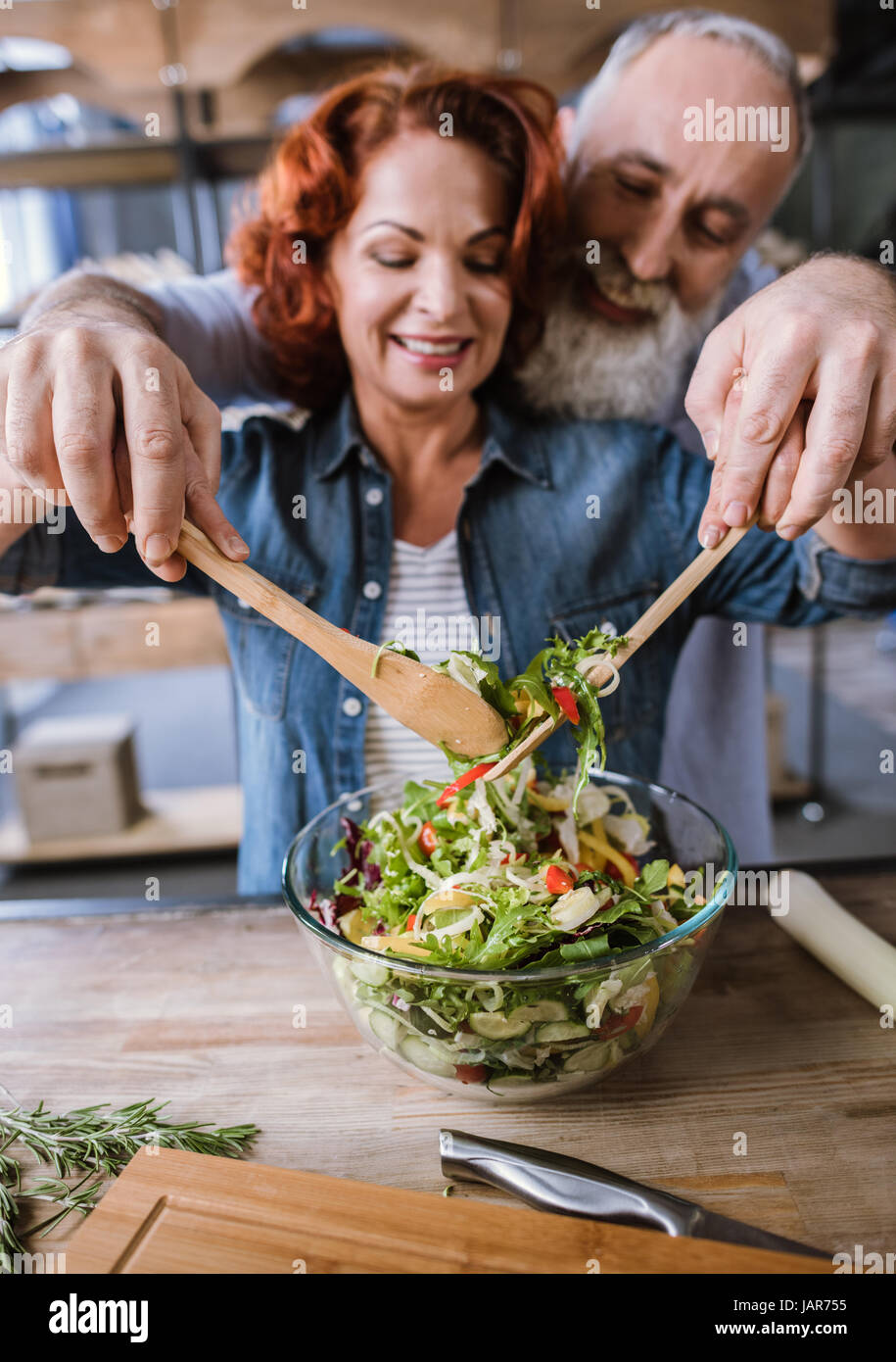 Couple cooking vegetable salad - Stock Image