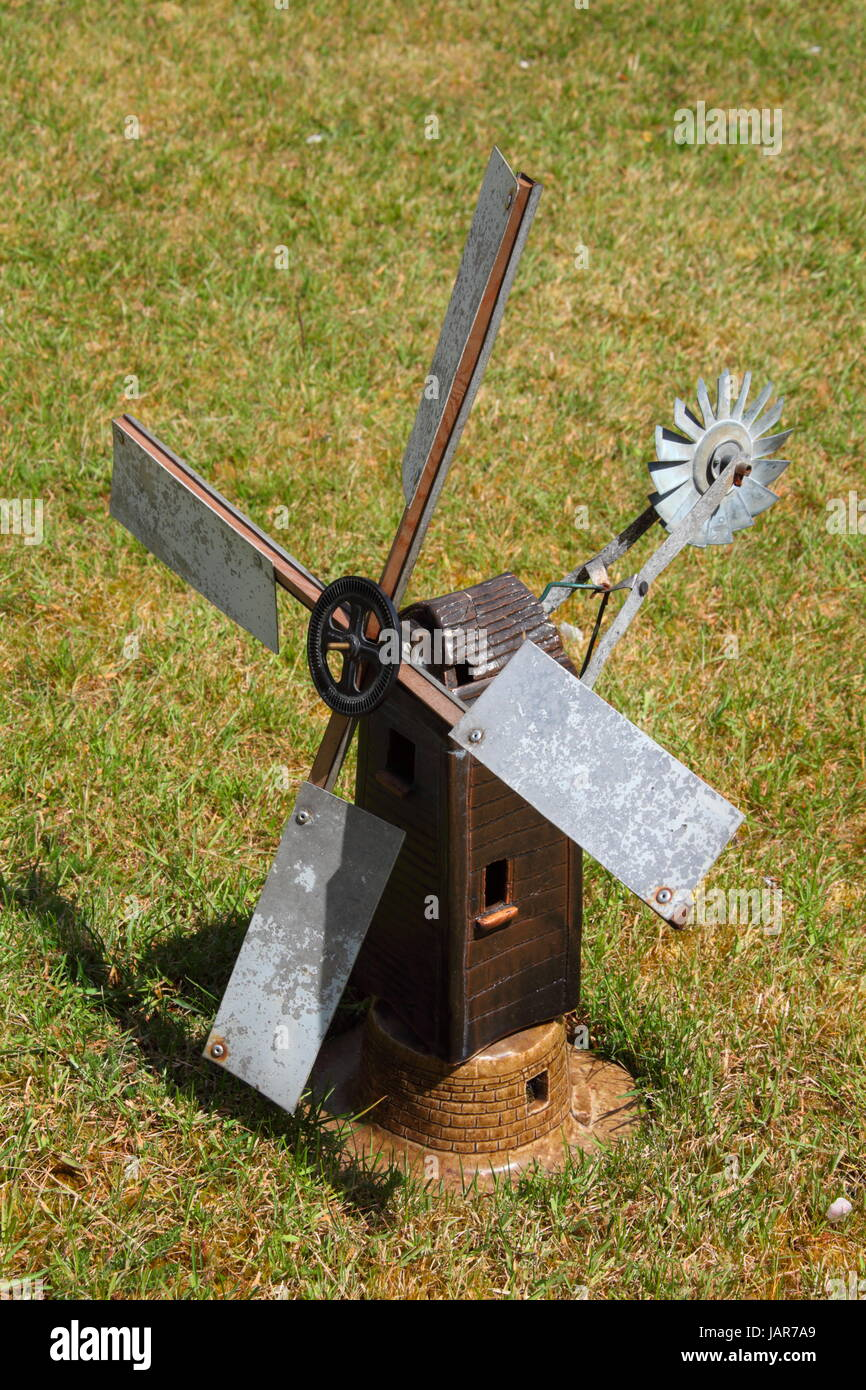 A hand made working windmill in the garden of the maker, made of fired clay, metal, and a few meccano components, - Stock Image
