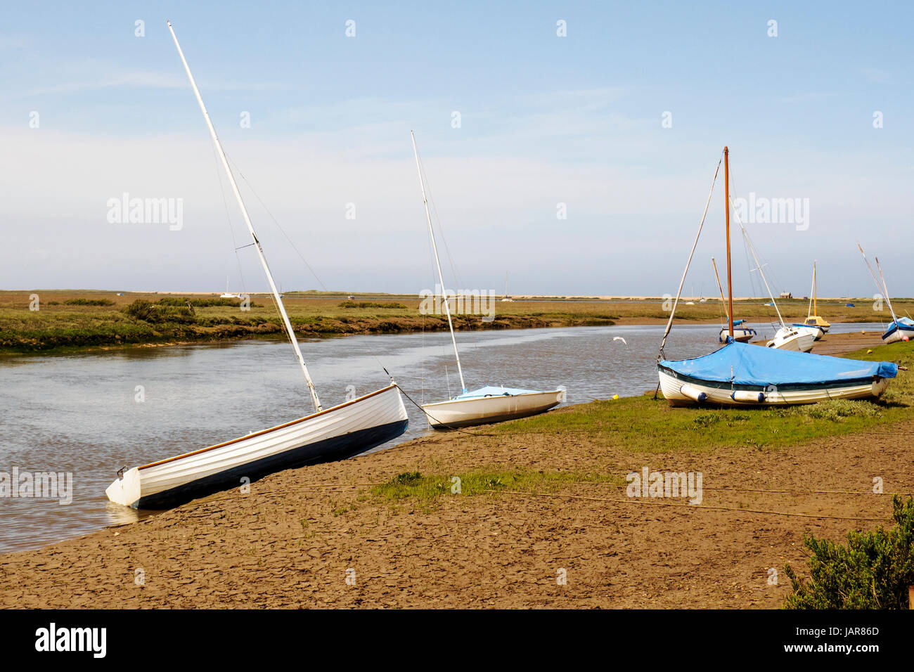 Small boats on the muddy shores of the New Cut channel through the salt marshes leading to Blakeney Quay in North Stock Photo