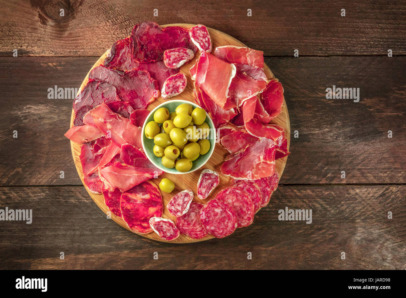 An overhead photo of a Spanish cold meats platter with jamon and payes sausage, with green olives, on a dark rustic - Stock Image
